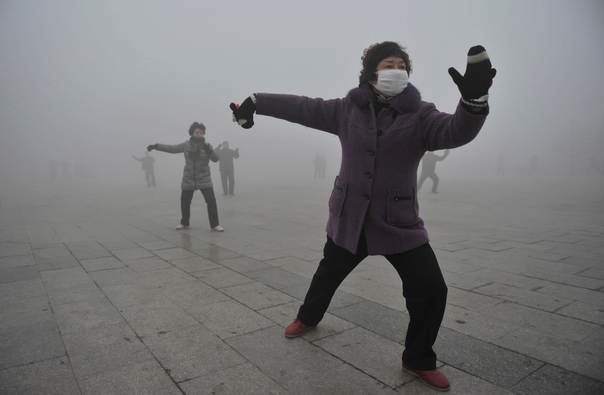 A woman wears a mask as she does her morning exercise outdoors in Fuyang, Anhui province, China, on January 14, 2013. REUTERS/China Daily