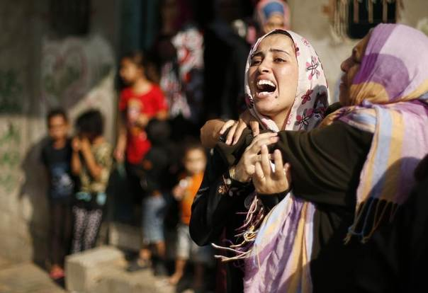 A Palestinian woman reacts after the death of her sister, whom medics said was killed in an Israeli air strike on a house, in Jabaliya refugee camp in the northern Gaza Strip, August 3, 2014. REUTERS/Suhaib Salem