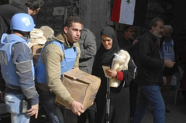 Residents receive food aid distributed by the U.N. Relief and Works Agency at the besieged al-Yarmouk camp, south of Damascus January 30, 2014, in this handout released by Syria's national news agency SANA. REUTERS/SANA/Handout via Reuters