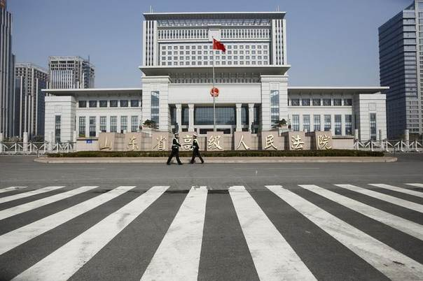 Policemen guard the entrance outside Shandong Province Supreme People's Court in Jinan, Shandong province, October 25, 2013. REUTERS/Aly Song