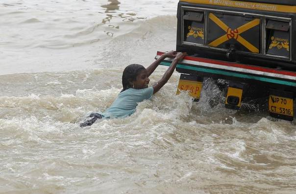 A girl plays as she holds onto a taxi through the flooded banks of river Ganga after heavy monsoon rains in the northern Indian city of Allahabad August 9, 2014. REUTERS/Jitendra Prakash