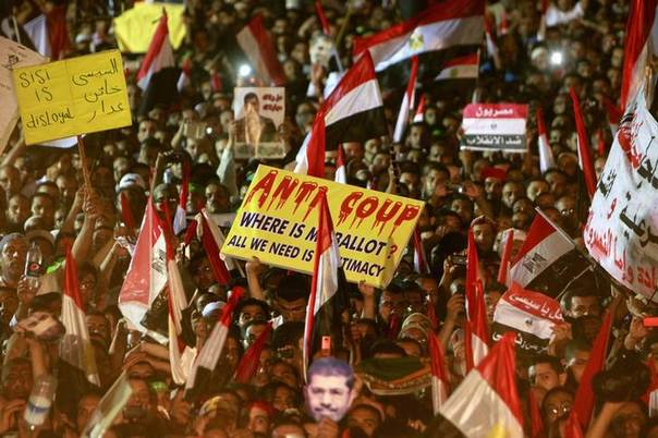 Members of the Muslim Brotherhood and supporters of deposed Egyptian President Mohamed Mursi wave Egyptian flags, signs and masks of him in Cairo July 12, 2013. REUTERS/Mohamed Abd El Ghany