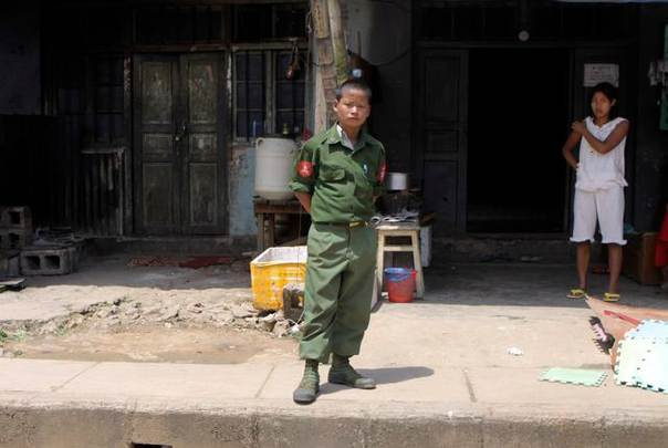 In a file photo from 2009, a child wearing a soldier's uniform looks at a convoy carrying diplomats and foreign journalists on a visit to Laukkai, capital of Myanmar's Kokang region. REUTERS/Khin Maung Win/Pool