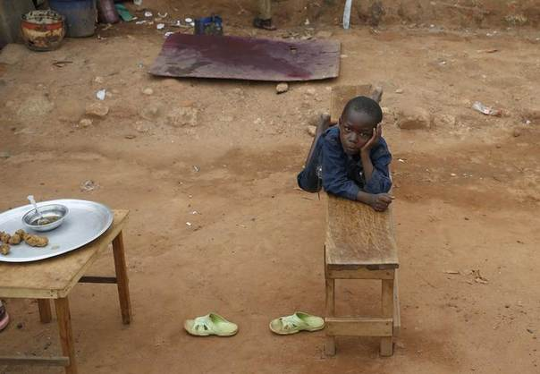 A boy rests after lunch in Bambari June 17, 2014. Picture taken June 17, 2014. REUTERS/Goran Tomasevic