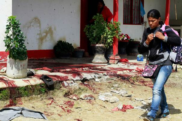 A woman walks by blood after an attack by criminal gangs on a farm in Santa Rosa, Antioquia, on Nov. 8, 2012. REUTERS/Albeiro Lopera