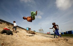 Youths somersault over old tyres in the Khayelitsha township, near Cape Town, South Afric
