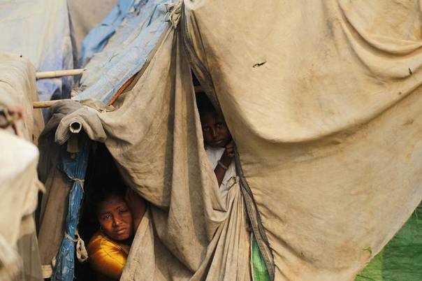Family members look from their temporary shelter at a Rohingya refugee camp as Myanmar's government embarks on a national census, in Sittwe April 2, 2014 REUTERS/Soe Zeya Tun