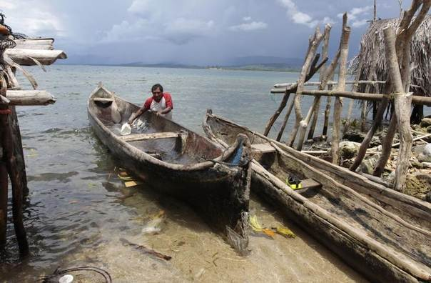 A Kuna fisherman cleans his boat in Carti, Kuna Yala, June 14, 2010. Rising seas from global warming, coming after years of coral reef destruction, are forcing thousands of indigenous Panamanians to leave their ancestral homes on low-lying Caribbean islands. REUTERS/Alberto Lowe
