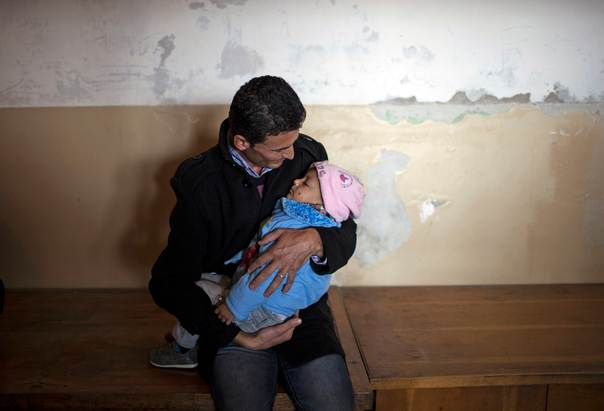 A Syrian man holds his child as he waits for medical supplies at a recently opened shelter in Vrazhdebna, near Sofia, on Dec. 3, 2013. REUTERS/Pierre Marsaut
