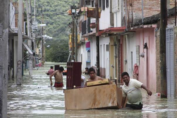 People move furniture through a flooded street in Tixtla, Mexico, Sept. 19, 2013. REUTERS/Stringer