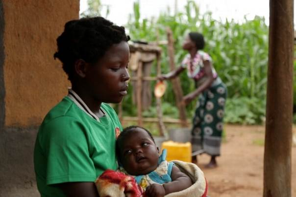 A 14-year-old girl holds her baby at her sister's home in a village in Kanduku, in Malawi's Mwanza district. She married in September 2013, but her husband chased her away. Her 15-year-old sister, in the background, married when she was 12. Both sisters said they married to escape poverty. HUMAN RIGHTS WATCH