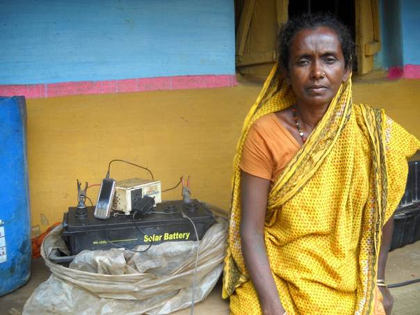 Champa Lohar sits listening to songs on her cell phone as it charges via an inverter attached to a solar battery in Kotpit village, in India's Odisha state, July 21 2013. TRF/Manipadma Jena