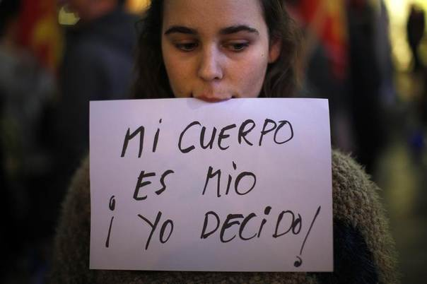 Adriana, 23, holds a sign with her mouth during a pro-choice protest against the government's proposed new abortion law in Malaga, southern Spain December 27, 2013. Spain's center-right government moved to make it harder for women to get an abortion, restricting a law that had allowed the procedure on request within a 14-week term, in a bid to rally core conservative support. The sign reads,