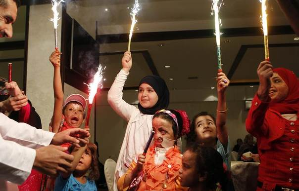 Syrian and Iraqi refugee children injured during violence in their countries hold up sparklers at an Eid al-Fitr party organised by the French humanitarian aid organisation Medecins Sans Frontieres (Doctors Without Borders) in Amman August 10, 2013. REUTERS/Ali Jarekji