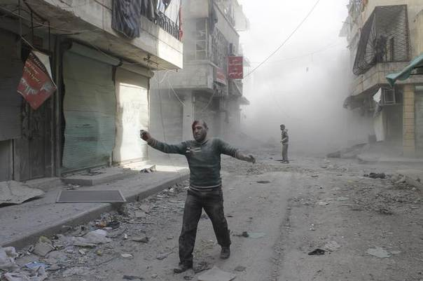 An injured man walks along a street after what activists said was a barrel bomb dropped by forces loyal to Syria's President Bashar al-Assad in Aleppo's al-Myassar neighbourhood April 16, 2014. REUTERS/Firas Badawi