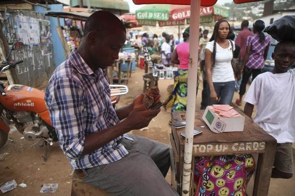 A telecoms agent sits at his stall at Lumley Junction in Sierra Leone's capital Freetown in this photo from December 2012. REUTERS/Simon Akam