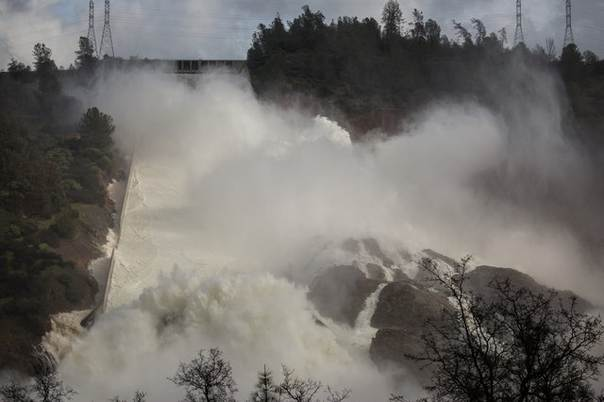 65,000 cfs of water flows through a damaged spillway on the