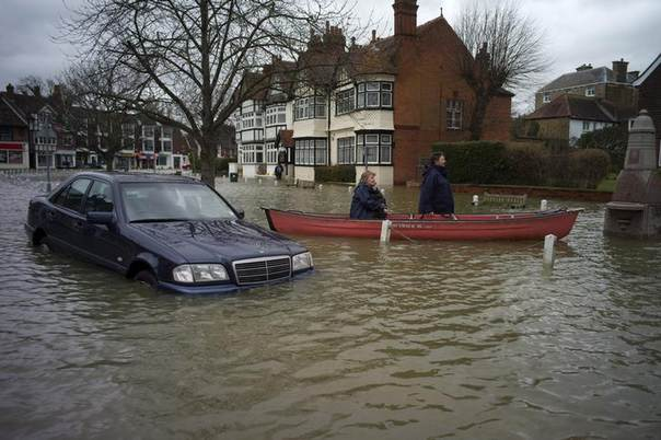 A man ferries a local resident by boat through the flooded central square in the village of Datchet in Berkshire, southern England February 12, 2014. REUTERS/Kieran Doherty
