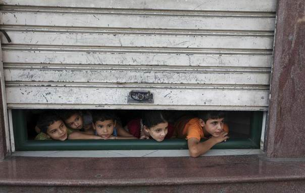 Palestinian children look through a store shutter at ambulances transporting casualties during Israeli offensive, in Gaza City July 30, 2014.  REUTERS/Ashraf Amrah