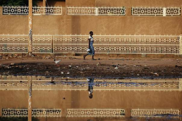 A woman is reflected in water as she walks in Niamey, Niger, September 15, 2013. Picture taken September 15, 2013. REUTERS/Joe Penney