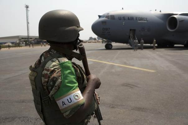 An African Union (AU) peacekeeper for the Central African Republic (MISCA) keeps guard as a U.S. Air Force plane lands carrying the first contingent of Rwandan AU soldiers at the capital Bangui, January 16, 2014. REUTERS/Siegfried Modola