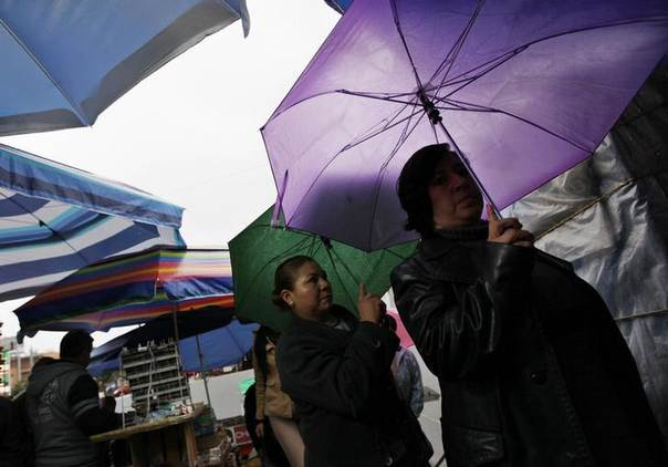 Women carry umbrellas as they walk in the rain at a market in Mexico City June 20, 2013. REUTERS/Claudia Daut
