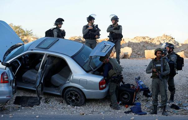 Israeli forces gather near a suspicious Palestinian car near