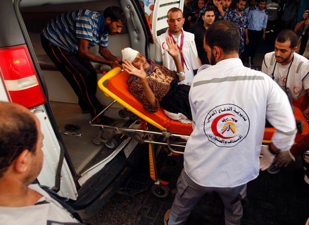 Palestinians wheel an elderly woman, who hospital officials said was wounded in an Israeli air strike, in Gaza City, on July 9, 2014. REUTERS/Ahmed Zakot