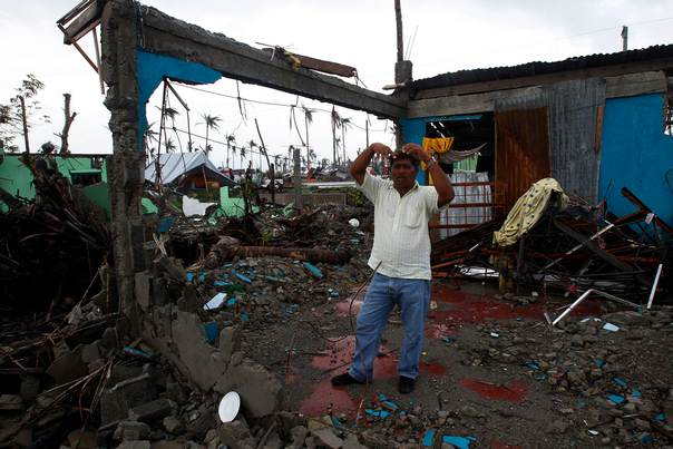 Pedro Lacandazo, 57, explains how seawater brought by the storm surge from super typhoon Haiyan flooded his house up to the ceiling and separated him from his family, in San Joaquin town at Palo, Leyte province, central Philippines, on  December 23, 2013.REUTERS/Romeo Ranoco