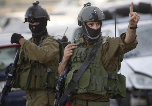 An Israeli soldier gestures as he takes part in an operation to locate three Israeli teens near the West Bank City of Hebron June 19, 2014. REUTERS/Mussa Qawasma