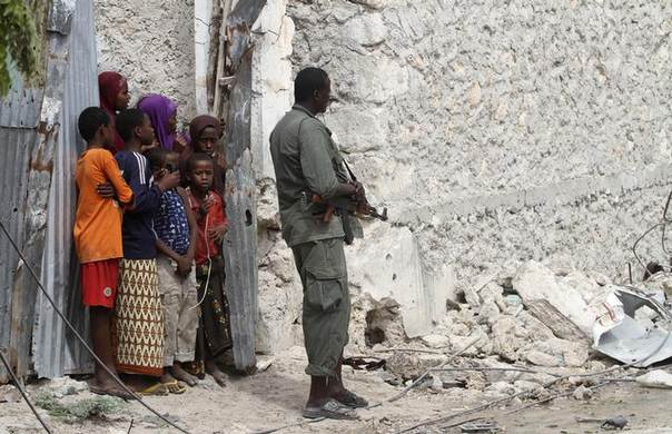 A Somali government soldier holds his position against suspected militants as residents watch during an attack at the Jilacow underground cell inside a national security compound in Mogadishu August 31, 2014. REUTERS/Feisal Omar