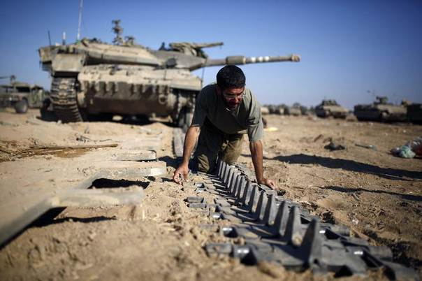An Israeli reserve soldier checks a tank track near the border with Gaza August 6, 2014. REUTERS/Amir Cohen