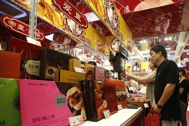 Consumers look at mooncakes in a shopping mall in Shanghai September 11, 2013. With more calories than a Big Mac, mooncakes are traditionally given as gifts to family, friends and employees during China's Mid-Autumn Festival. REUTERS/Aly Song