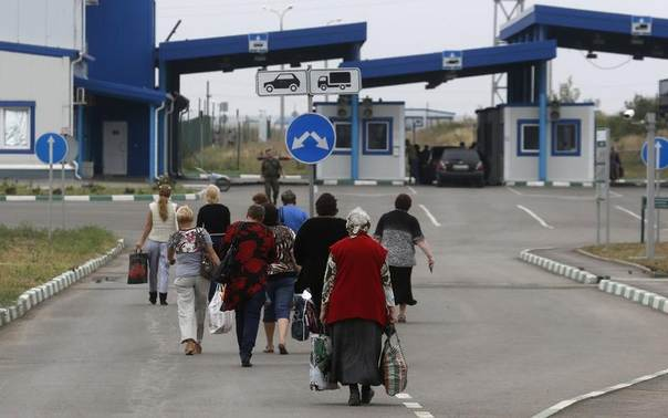 Ukrainian citizens walk from Russia into Ukraine at border crossing point Donetsk, in Russia's Rostov Region, August 19, 2014. REUTERS/Alexander Demianchuk