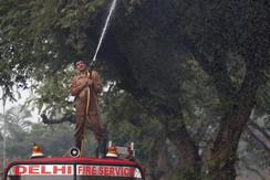 A firefighter sprays water onto trees to fight the air pollution in Delhi, India