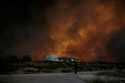 Black smoke rises behind a house as a wildfire burns near the village of Varnavas, north of Athens, Greece