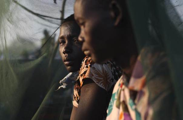 Two woman displaced by the fighting in Bor county sit by a mosquito net during the early morning in Minkaman, in Awerial county, Lakes state, in South Sudan, January 15, 2014. REUTERS/Andreea Campeanu