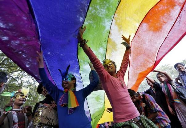 Participants dance under a a rainbow flag as they attend the sixth Delhi Queer Pride parade, an event promoting gay, lesbian, bisexual and transgender rights, in New Delhi, India, November 24, 2013. REUTERS/Mansi Thapliyal
