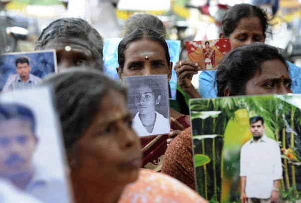 Sri Lankan Tamils hold pictures of family members who disappeared during the war against the Liberation Tigers of Tamil Eelam (LTTE) at a protest in Jaffna, about 400 km (250 miles) north of Colombo November 15, 2013. REUTERS/Stringer