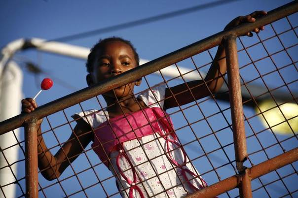 A girl holds a lollipop as she watches from behind a fence at other children playing on the street below in Zanzibar, Tanzania, November 22, 2007. REUTERS/Finbarr O'Reilly