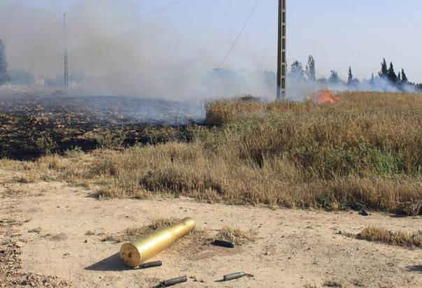 An empty ammunition casing and a fire are seen in a field after heavy fighting between Free Syrian Army fighters, and the forces of Syrian President Bashar al-Assad and Lebanon's Hezbollah at the al Barak area near Qusair town May 31, 2013. REUTERS/ Rami Bleible