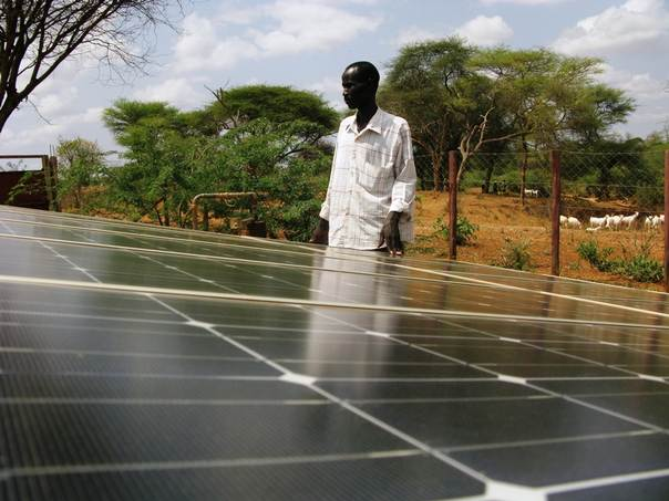 A man stands near a solar panel which powers a borehole well in Kenya. THOMSON REUTERS FOUNDATION/Geoffrey Kamadi