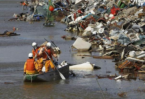 Firefighters search for victims on a boat at an area devastated by the March 11 earthquake and tsunami, in Sendai, Miyagi prefecture, Japan, April 16, 2011. REUTERS/Toru Hanai