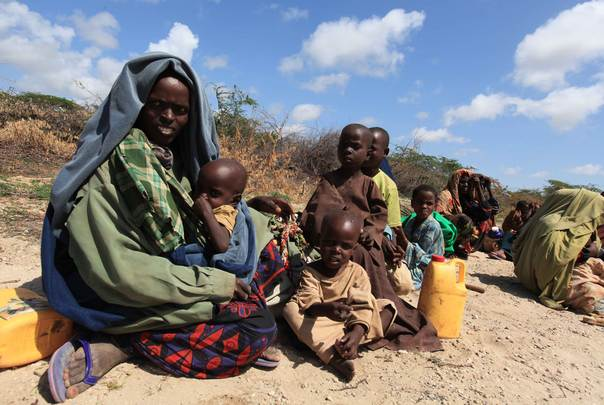 An internally displaced woman and her children sit on their belongings after arriving at a temporary camp in the Hodan district of Somalia's capital Mogadishu on August 21, 2011. REUTERS/Feisal Omar