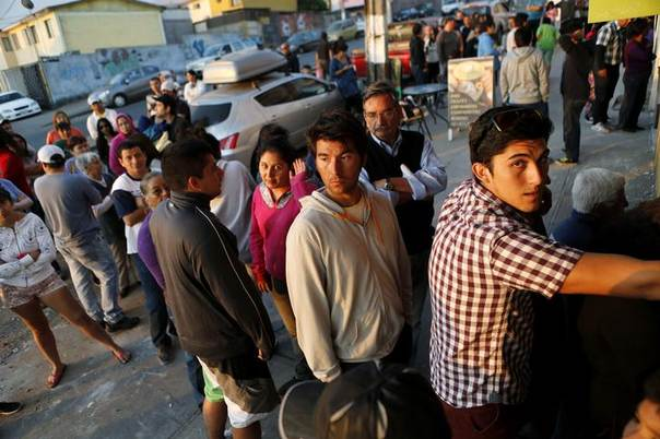 People line up outside a store after an earthquake and tsunami hit the northern port of Iquique April 2, 2014. REUTERS/Ivan Alvarado