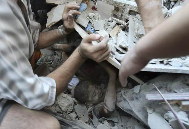Palestinians rescue Mahmoud al-Ghol, 10, from the rubble of a house in Rafah in the southern Gaza Strip after an Israeli air strike. Picture August 3, 2014, REUTERS/Ibraheem Abu Mustafa