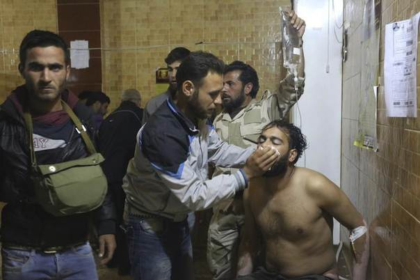 People treat a man affected by what activists say was a gas attack in Kfar Zeita village, inside a hospital in the central province of Hama, Syria, May 19, 2014. REUTERS/Badi Khlif