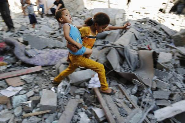 A Palestinian girl carries a child across rubble from a building that police said was destroyed by an Israeli air strike, in the Burij refugee camp in the central Gaza Strip August 1, 2014. REUTERS/Finbarr O'Reilly