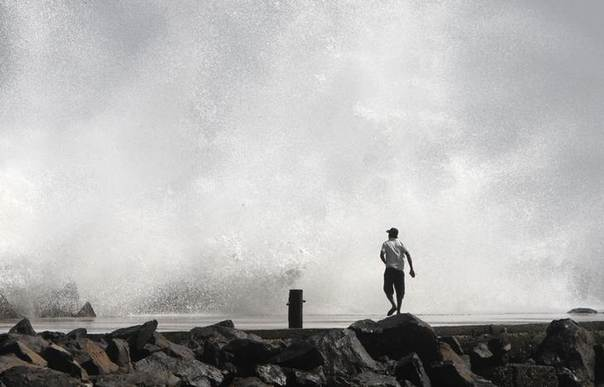 A man watches a large wave at a fishing harbour in Chennai before the landfall of Cyclone Thane, December 28, 2011. REUTERS/Babu