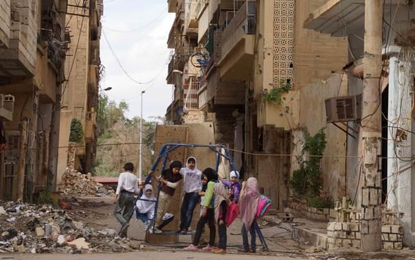 Girls play on a swing in a damaged street full of debris in Deir al-Zor May 21, 2013. REUTERS/Khalil Ashawi. www.trust.org